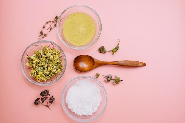 Pó de colágeno ou argila amarela com flores secas e sal marinho na superfície rosa pastel com colher de pau. estilo liso leigo. cuidados com a pele em casa. boticário moderno