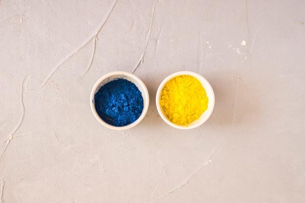 Pó de cor amarelo e azul holi em tigelas brancas sobre fundo de concreto