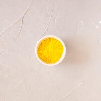Pó de cor amarelo holi na tigela branca sobre fundo de concreto