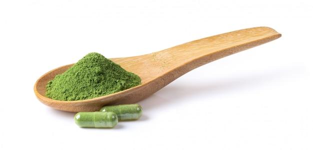 Pó de ervas kariyat verde e cápsula na colher de madeira em branco