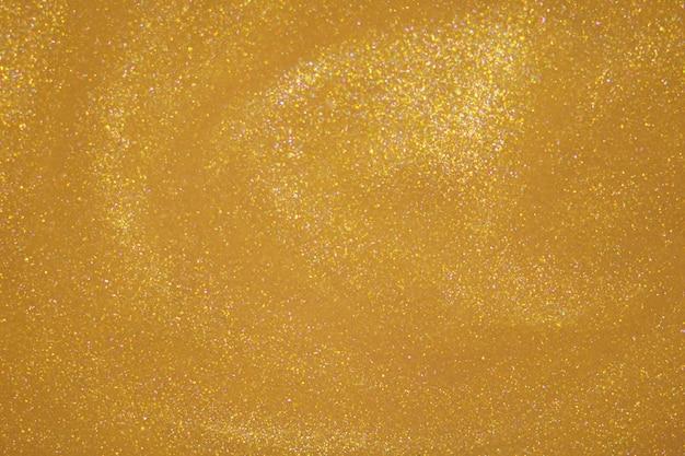 Pó de glitter dourado em fundo escuro.
