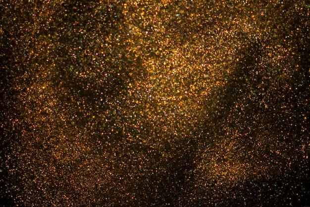 Pó de glitter dourado em fundo escuro