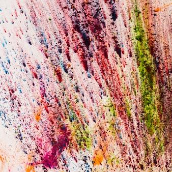 Pó de holi colorido indiano espirrando em fundo branco