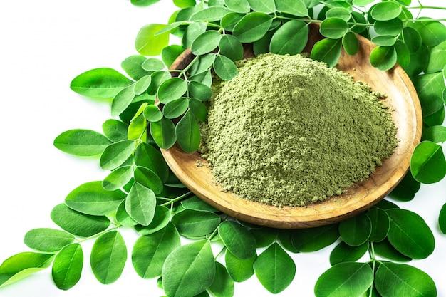 Pó de moringa (moringa oleifera) em uma tigela de madeira com as folhas frescas originais de moringa, isoladas no branco.