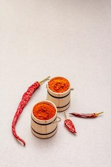 Pó de páprica doce e quente vermelho magiar (húngaro). tempero tradicional para cozinhar comida nacional, diferentes variedades de pimenta seca. barris de madeira,