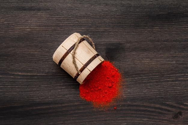 Pó de páprica doce vermelho brilhante magiar. tempero tradicional para cozinhar comida nacional. barril de madeira, preto de madeira