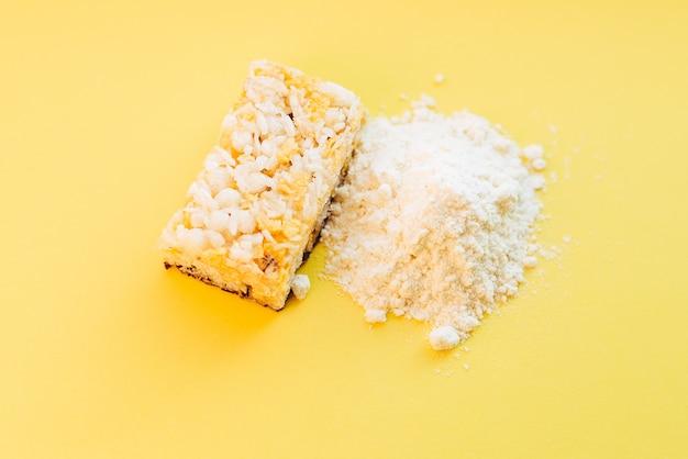 Pó de proteína de soro de leite e barra de proteína de cereais na parede amarela.
