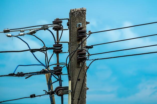 Pó elétrico com isoladores e fios no céu azul