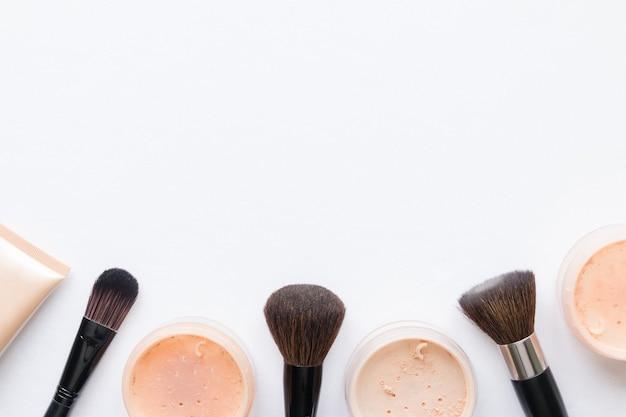 Pó facial e pincel para maquiagem em um fundo branco