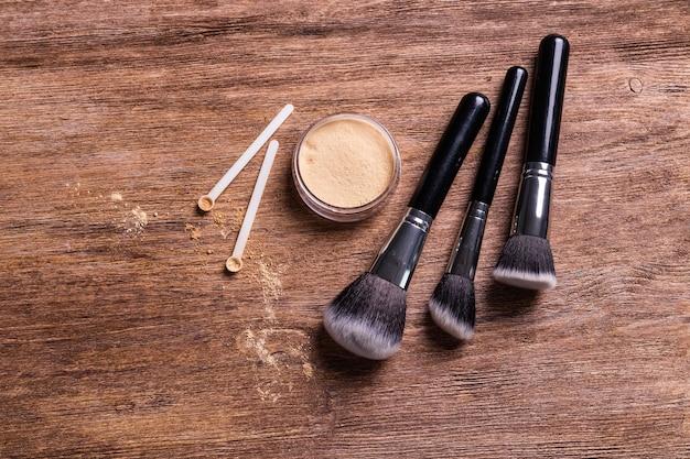 Pó mineral de cores diferentes com dispensador de colher para maquilhagem em fundo de madeira.