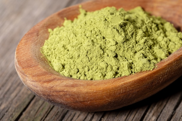 Pó verde japonês do chá do matcha na colher de madeira na placa de madeira dilapidada velha.