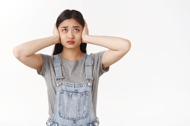 Pobre aluna linda morena asiática não suporta barulhos altos não consegue estudar dormitório barulhento olhar para cima perturbado descontente franzindo a testa reclamando vizinhos ignorantes, ouvidos fechados