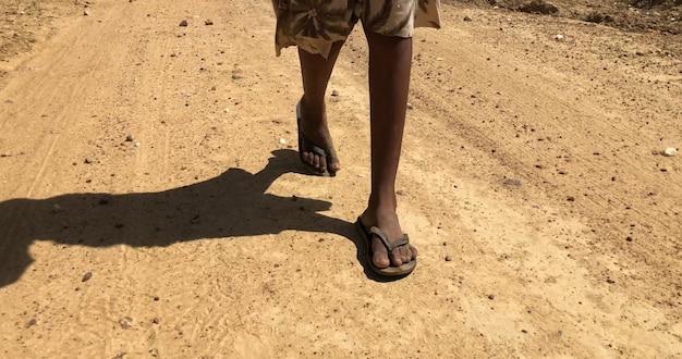 Pobre criança andando em uma estrada de terra em um dia quente e ensolarado.