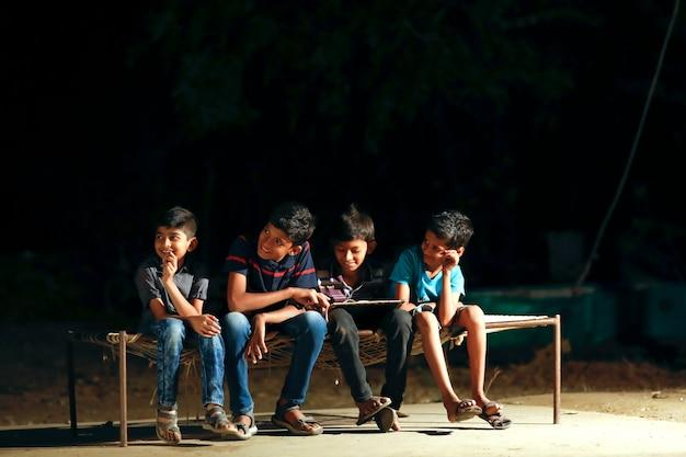 Pobre criança fazendo sua lição de casa na luz da rua