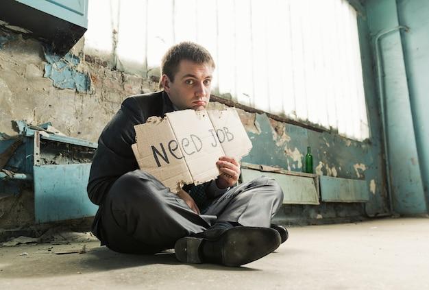Pobre empresário segurando uma placa pedindo emprego