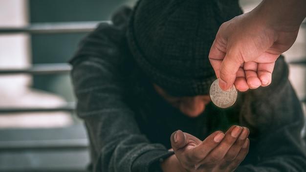 Pobre homem desabrigado ou refugiado sentado no chão sujo, recebendo dinheiro.