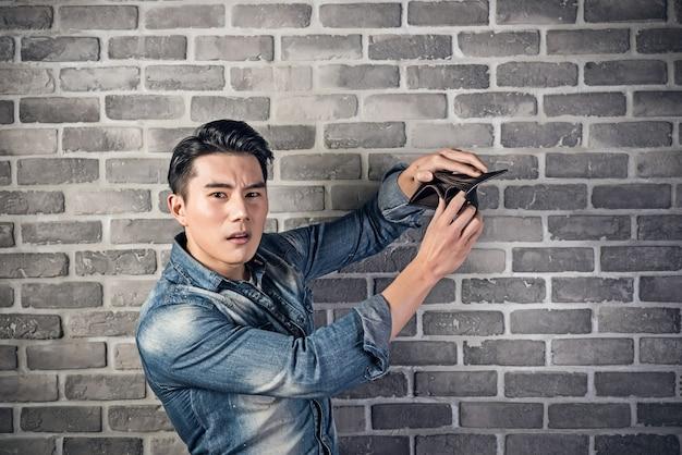 Pobre jovem asiático segurando a carteira vazia