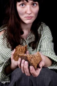Pobre mendigo mulher com um pedaço de pão.