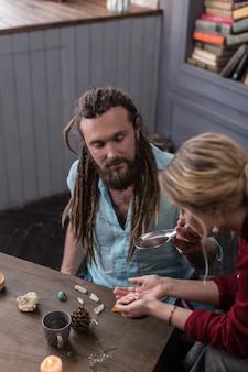 Poção especial. homem barbudo simpático olhando para as mãos femininas enquanto segura uma colher com uma poção especial