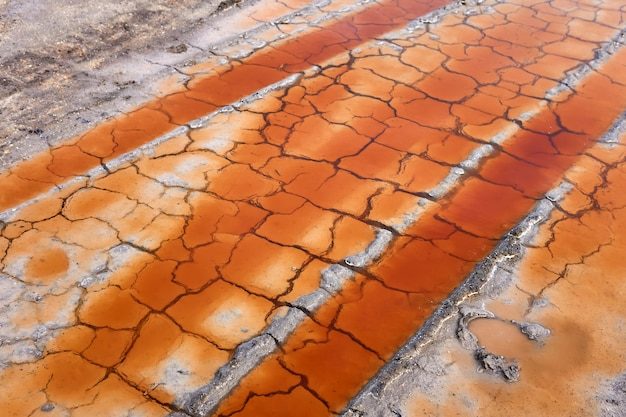 Poças nos rastros das rodas dos carros no solo de argila rachada do deserto