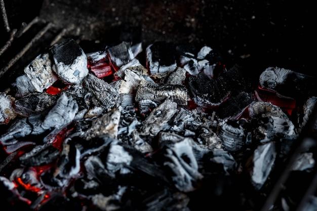 Poço da grade do bbq com briquetes de carvão quentes de incandescência e flamejantes, parede ou textura do alimento, lenha ardente na lareira perto acima, fogo do bbq, parede do carvão vegetal. fogo de carvão com faíscas. fogo