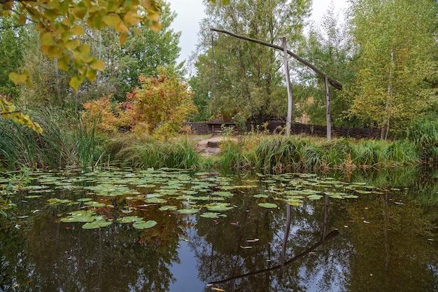 Poço de madeira velho. parque do outono. árvores refletidas na água do lago do parque
