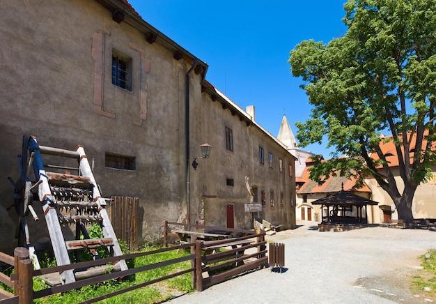 Poço e instrumento de tortura no pátio do castelo medieval krivoklat, na república tcheca