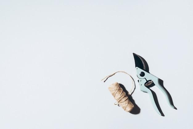 Podador de ramo e linhas de linho de artesanato sobre fundo cinza.