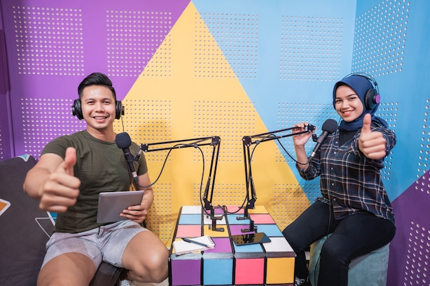 Podcast de homem e mulher em estúdio e mostrando o polegar