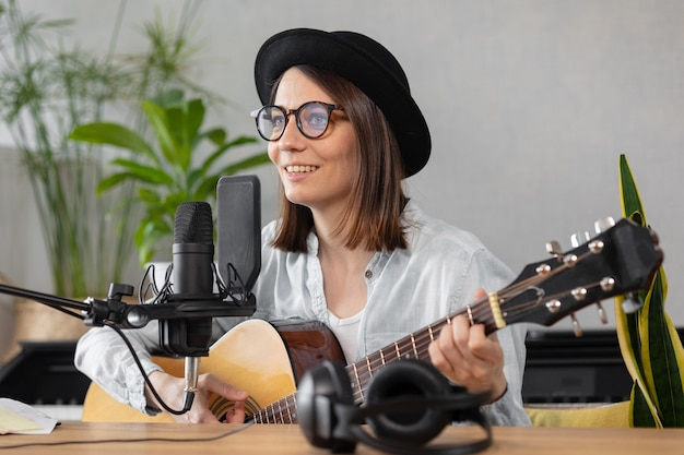 Podcast música criação de conteúdo de áudio, bela mulher europeia podcaster de chapéu com uma guitarra ou