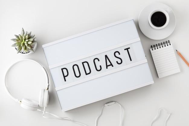 Podcast palavra na mesa de luz com fones de ouvido na mesa branca