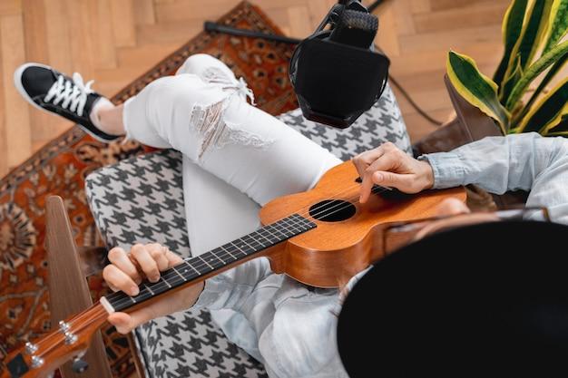 Podcaster cria conteúdo mulher musica feliz com gravações de violão podcast com microfone e