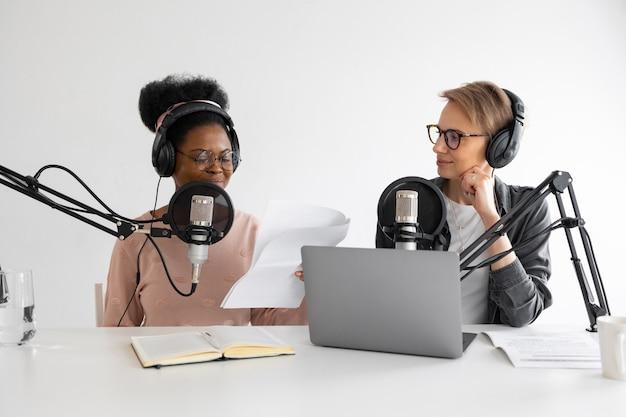Podcasters mulher afro-americana e europeia com fones de ouvido e microfone