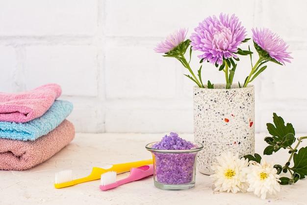 Pode com flores de ásteres, toalhas, sal marinho e escovas de dente em um fundo branco. cosméticos femininos e acessórios de lavagem.