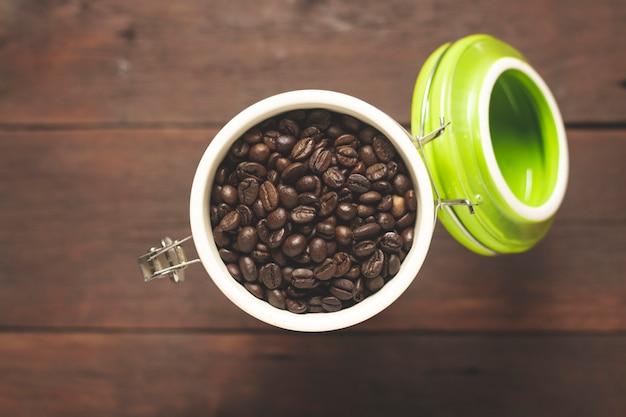 Pode com grãos de café sobre uma mesa de madeira. bandeira. conceito de café, plantação, processamento, coleta. vista superior, configuração plana