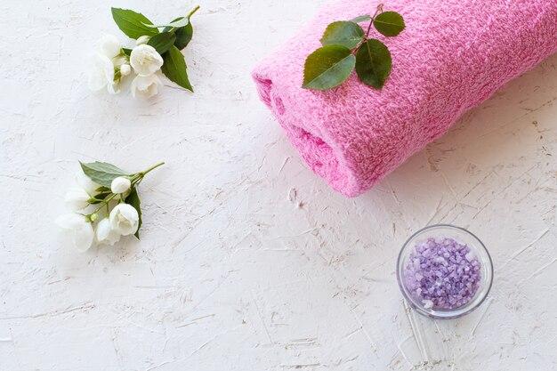 Pode com sal marinho, toalha e flores de jasmim em um fundo branco. produtos femininos para spa. vista do topo.