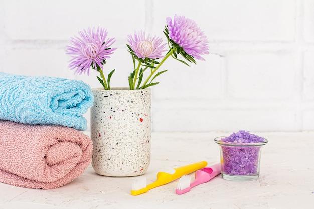 Pode com sal marinho, toalhas, escovas de dentes e flores de ásteres em um fundo branco. cosméticos femininos e acessórios de lavagem.