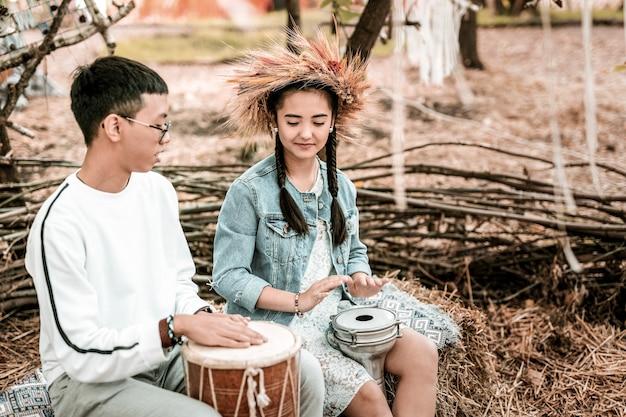 Pode fazer isso. moreno satisfeito sentado em semi-posição e ensinando sua parceira a fazer música