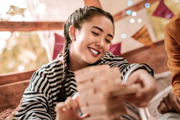 Pode fazer isso. mulher atraente de cabelos compridos mantendo um sorriso no rosto enquanto tira um detalhe de madeira