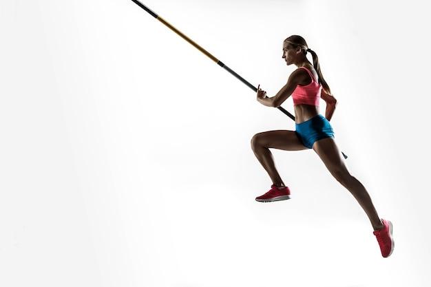 Poder, beleza e pureza. treinamento profissional de salto com vara feminino em estúdio branco