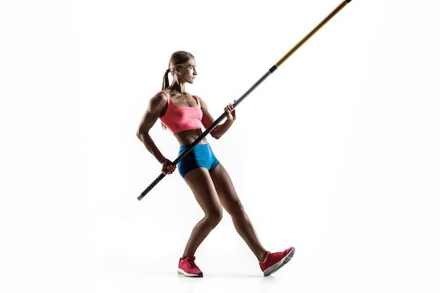 Poder, beleza e pureza. treinamento profissional de salto com vara feminino na parede branca. praticando modelo feminino apto e magro. conceito de esporte,