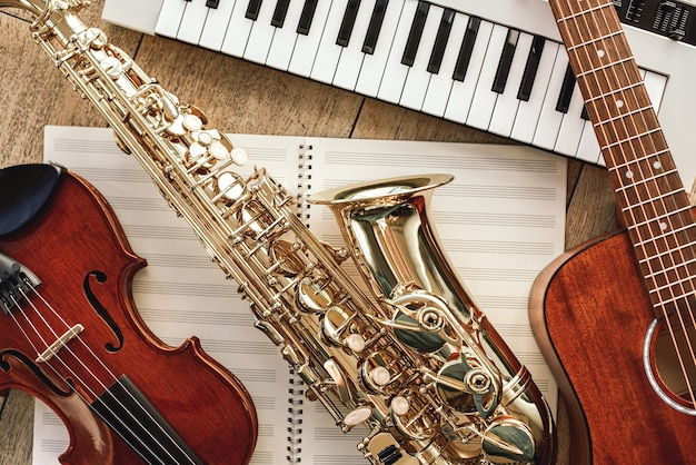 Poder da música vista superior de instrumentos musicais conjunto sintetizador, guitarra, saxofone e violino deitado