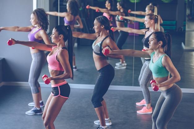 Poder das meninas. vista lateral de jovens mulheres bonitas em roupas esportivas com corpos perfeitos se exercitando com halteres na academia