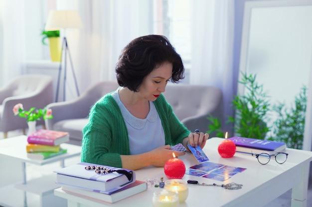 Poder de pensamento. bela mulher séria pegando um cartão enquanto se concentra em sua tarefa