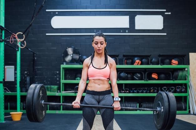 Poder interior da jovem mulher que treina o gym indoor sozinho
