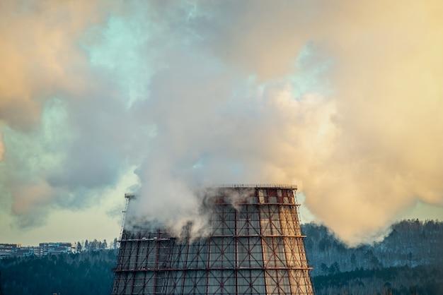 Poderosa chaminé de fábrica industrial está fumegando e emitindo dióxido de carbono no meio ambiente