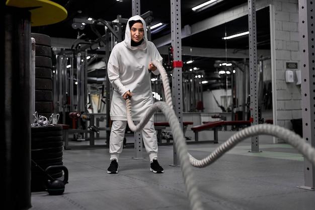 Poderosa treinadora de cross fit em hijab árabe faz treino de batalha com cordas sozinha na academia, concentrada em exercícios com equipamentos esportivos