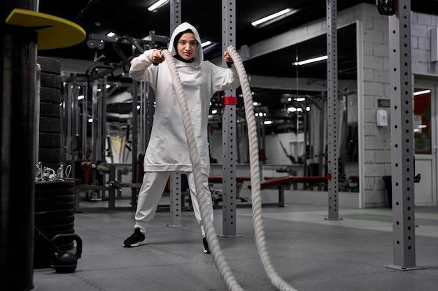 Poderosa treinadora de crossfit árabe em hijab faz treino de batalha com cordas sozinha na academia, concentrada em exercícios com equipamentos esportivos