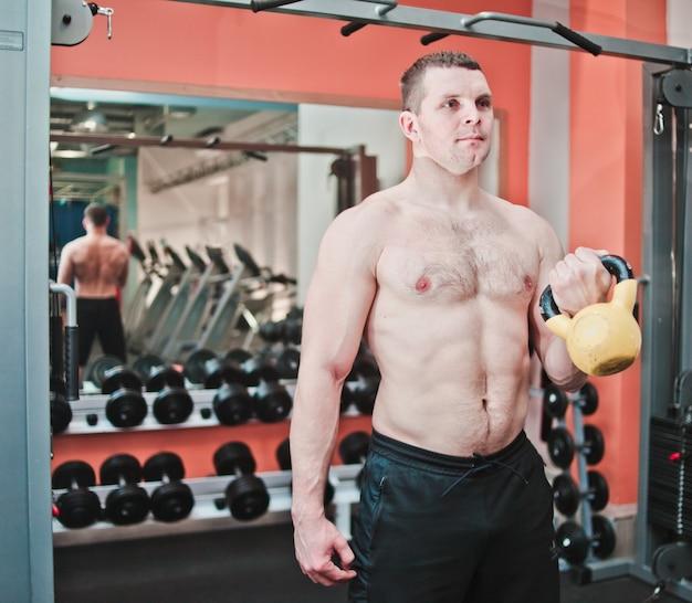 Poderoso e forte. atlético homem com torso nu, fazendo exercícios com kettlebell no ginásio
