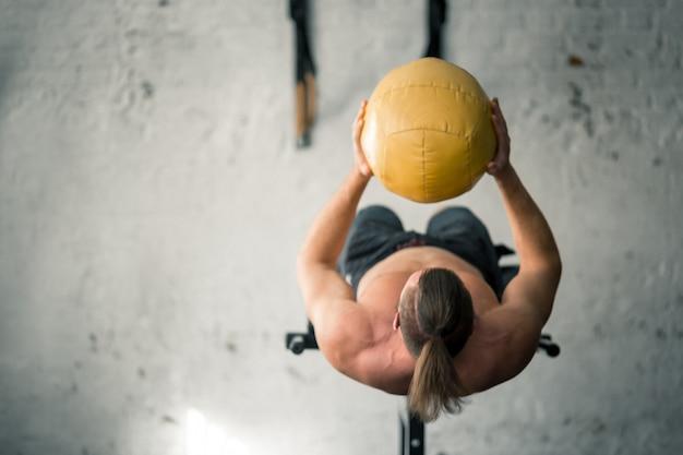 Poderoso homem atlético, realizando exercícios abdominais com bola medicinal